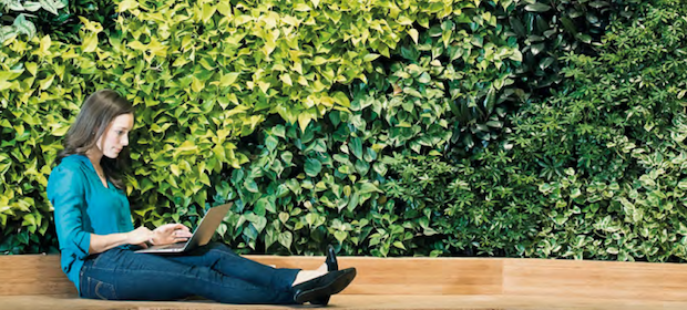 Eine Frau sitzt mit ihrem Laptop auf dem Boden vor einer grünen Hecke.