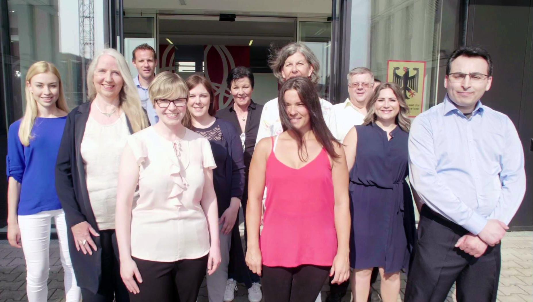 Mitarbeiter des Beschaffungsamts des BMI stehen vor dem Eingangsbereich der Behörde.