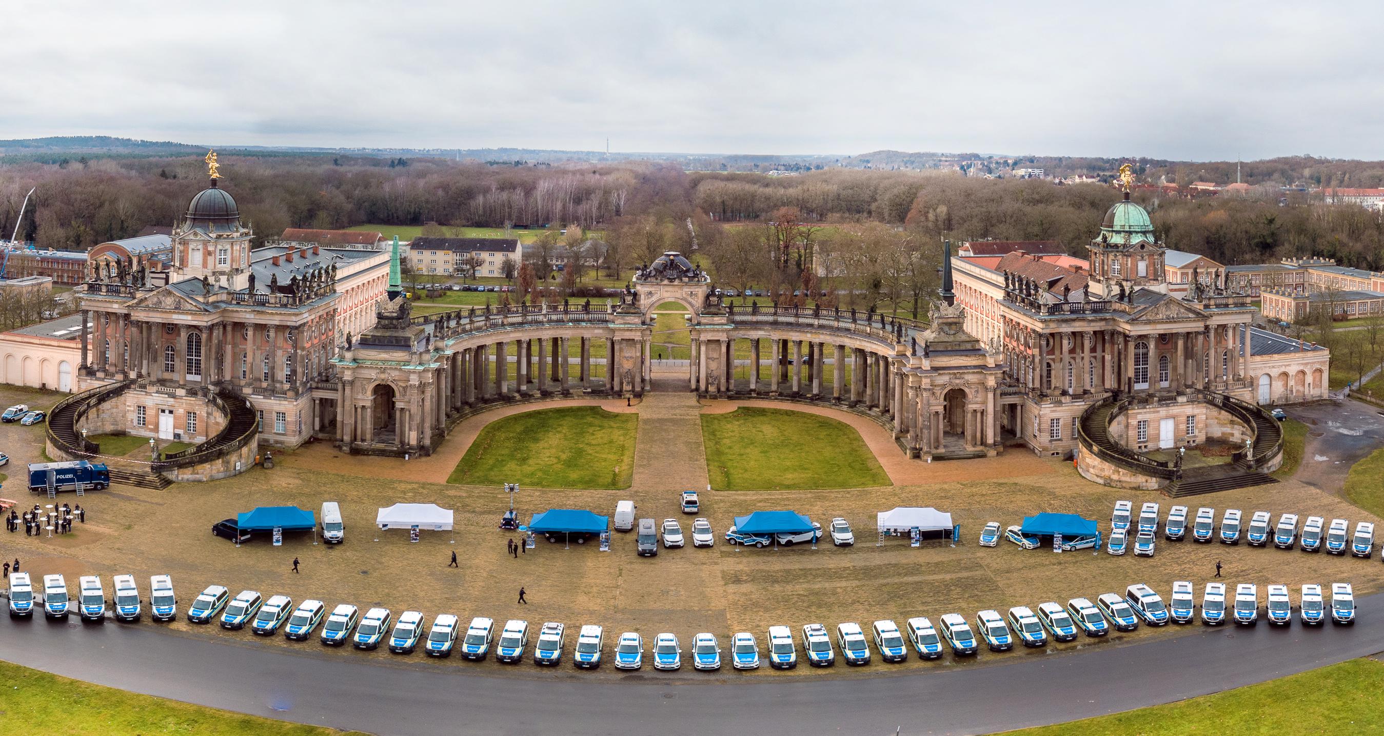 Vogelperspektive auf das Potsdamer Schloss Sanssouci. Im Vordergrund Fahrzeuge der Bundespolizei.