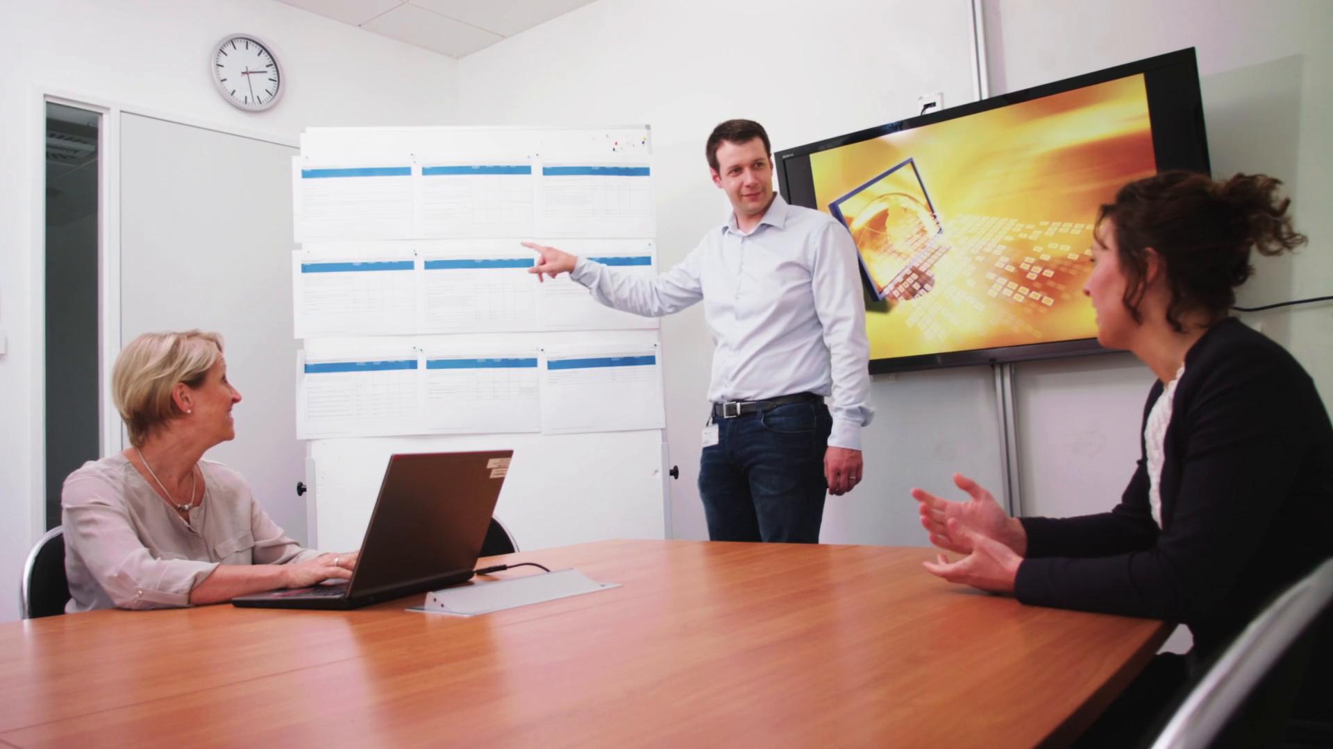 Mitarbeiter des BeschA in einem Meeting. Im Hintergrund sind ein Monitor und eine Tafel zu sehen.