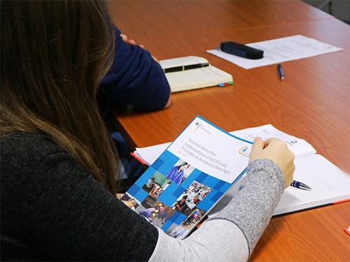Bild: Teilnehmerin der Schulung hält den aktuellen Nationalen Aktionsplan Wirtschaft und Menschenrechte (NAP) in der Hand.