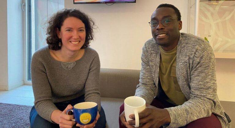 Bild:Marion Rumpl und Patrick Nyakoojo sitzend im Foyer