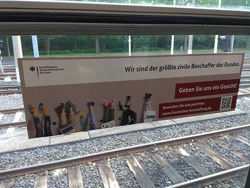 Bild: Ein Plakat mit Fachinformationen und einem Motiv auf der Seitenscheibe einer Bahn