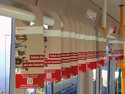 Bild: Karten mit Fachinformationen hängen an den Haltegriffen eines Busses
