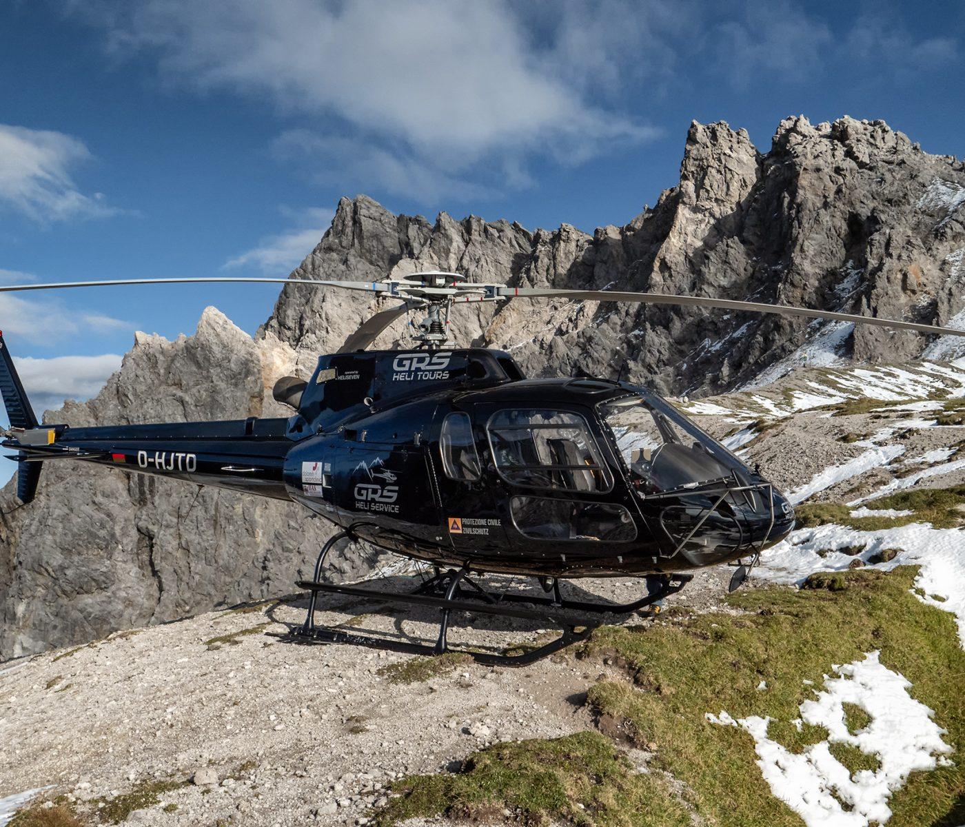 Ein Helikopter steht auf dem Gipfel eines Berges in den Alpen. Der Helikopter wurde für die Durchführung einer Schweremesskampagne angemietet.
