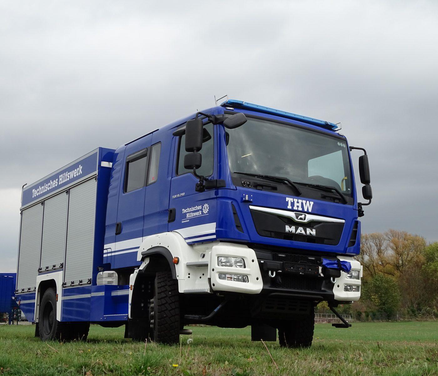 Auf einer Wiese steht ein Gerätekraftwagen des THWs (Bundesanstalt technisches Hilfswerk).