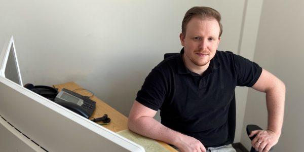 Bild: Unser Mitarbeiter Max Kühn sitzend am Schreibtisch